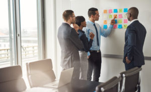 56127887 - diverse group of four business people gathered around white board with sticky notes planning something